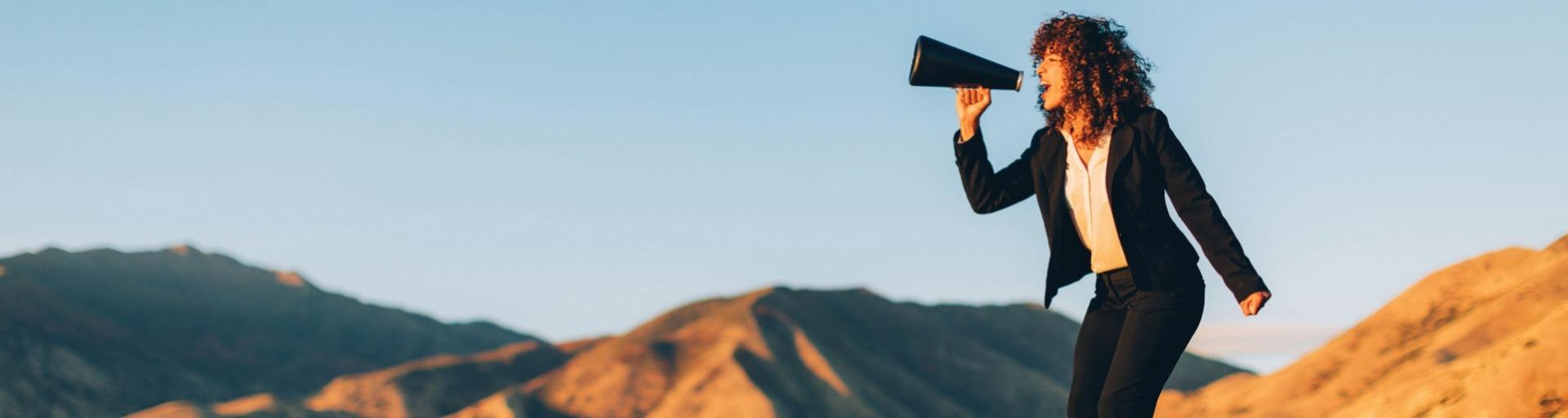 Zakenvrouw schreeuwt door een megaphone